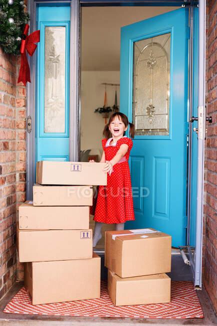 Ragazza in piedi davanti alla porta con consegna di scatole — Foto stock