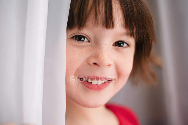 Portrait of a girl standing by a curtain — Stock Photo