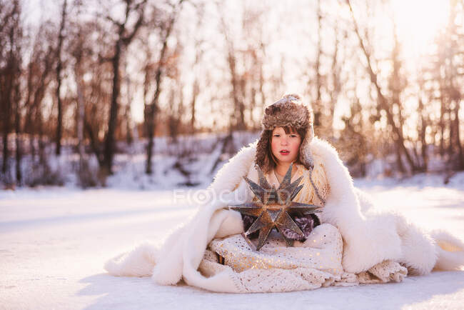 Girl dressed as snow queen sitting in the snow — Stock Photo