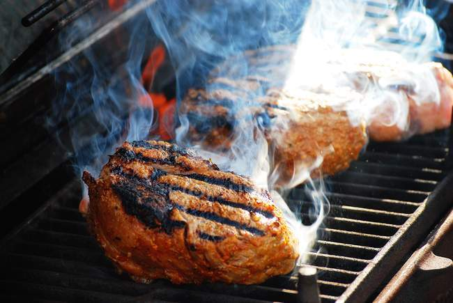 Steaks grilling on a barbecue, closeup view — Stock Photo