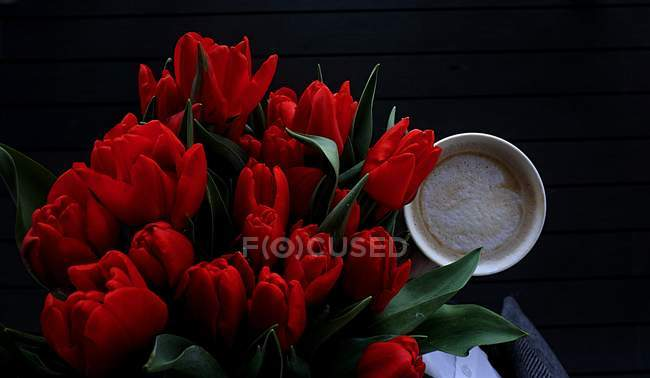 Overhead view of tulips and cup of coffee — Stock Photo