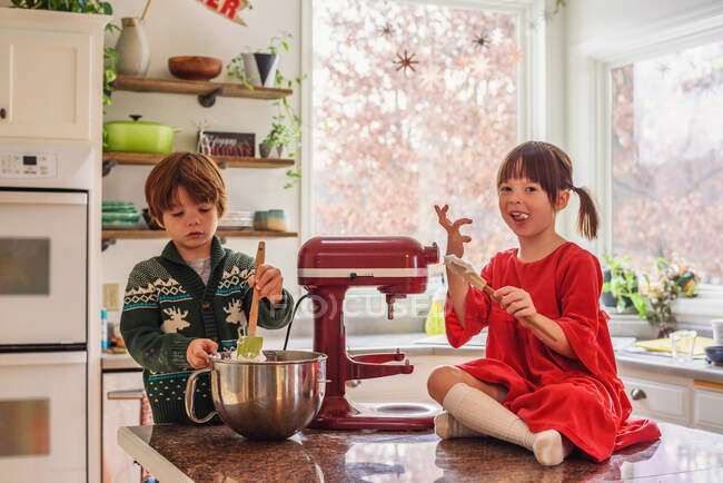 Two children helping bake cookies together in the kitchen — Stock Photo
