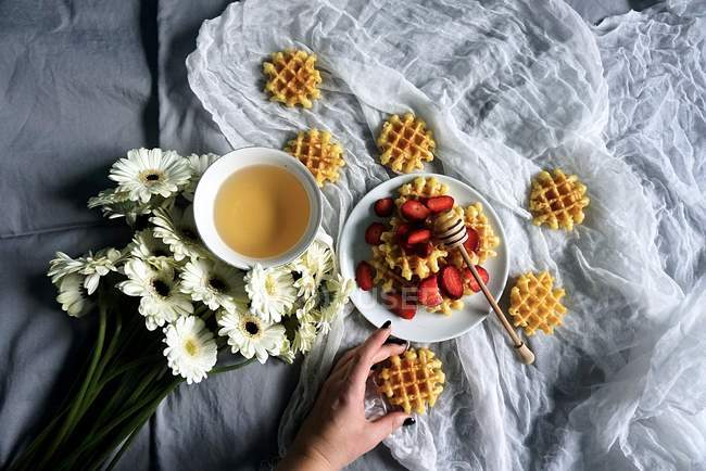 Woman hand and breakfast waffles, top view — стокове фото