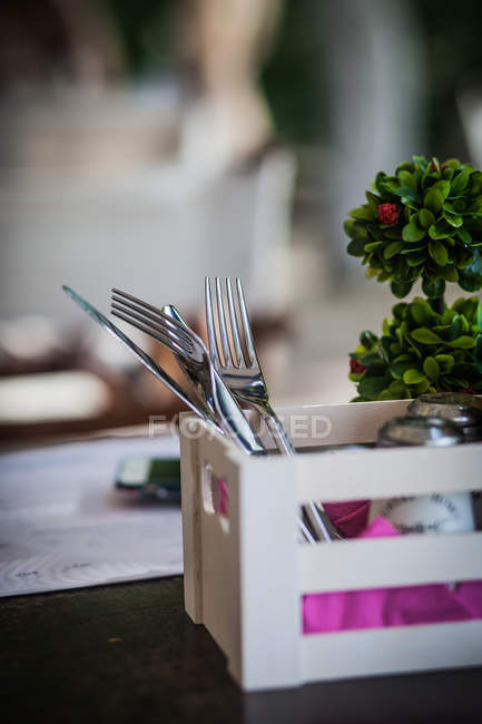 Knives and forks in wooden box on table in restaurant - foto de stock