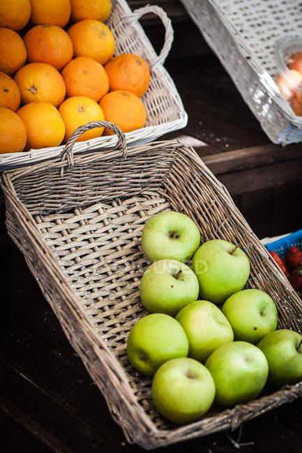 Oranges et pommes dans des paniers au marché aux fruits — Photo de stock