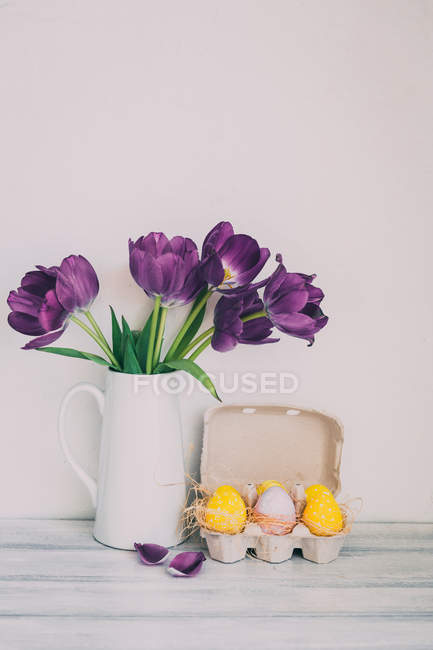 Tulips in a jug with box of Easter eggs — Stock Photo