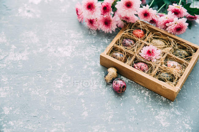 Multi-colored Easter eggs and flowers over rustic background — Stock Photo
