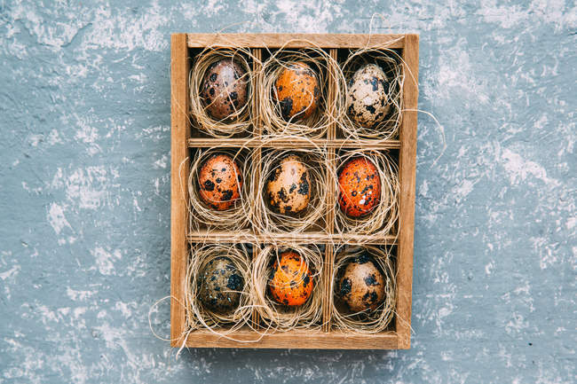 Easter eggs in a wooden box over weathered background — Stock Photo