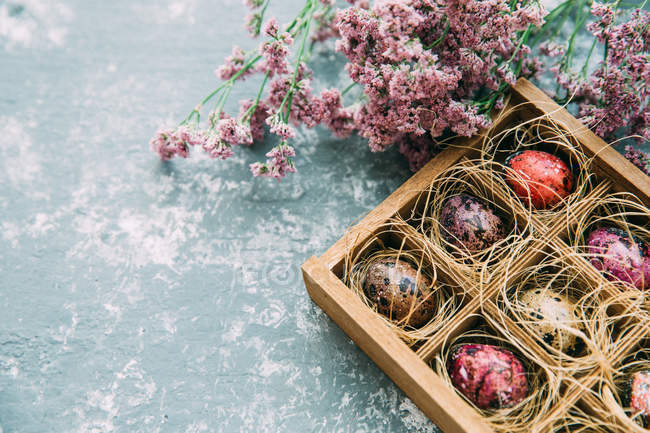 Multi-colored Easter eggs and flowers over weathered background — Stock Photo