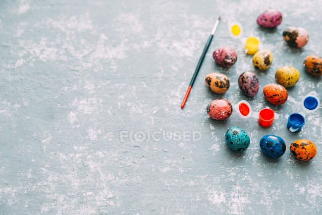 Multi-colored Easter eggs and paint over weathered background — Stock Photo