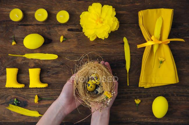 Жовтий прикраси і руки дівчина Холдинг гніздо з великодні яйця — стокове фото