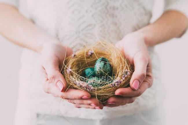 Жінка тримає гнізда з великодні яйця — стокове фото