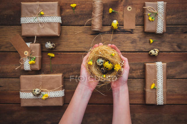 Wrapped gifts and girl hands holding a nest with Easter eggs — Stock Photo