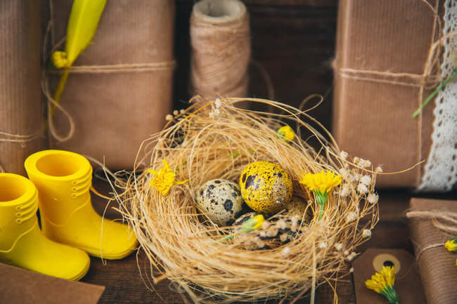 Easter decorations setting with boots and eggs in nest — Stock Photo