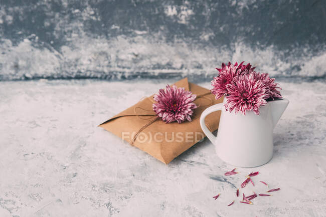 Envelope and jug with pink flowers — Stock Photo