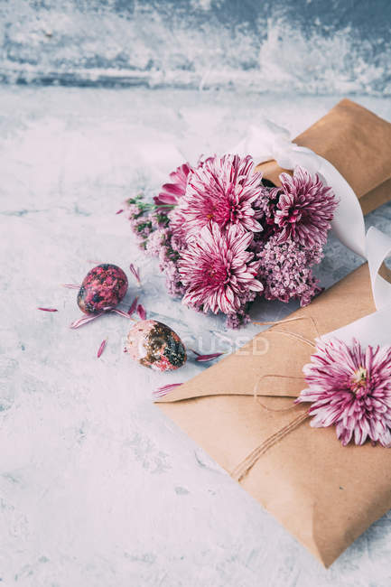 Envelope and vase with pink flowers and Easter eggs — Stock Photo