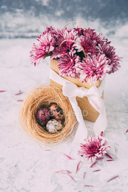 Pink flowers in a paper bag and Easter eggs — Stock Photo