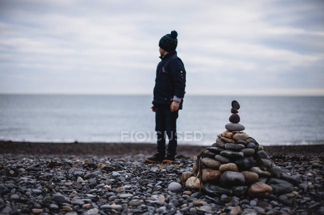 Boy standing on beach by a stack of pebbles, Ireland — Stock Photo