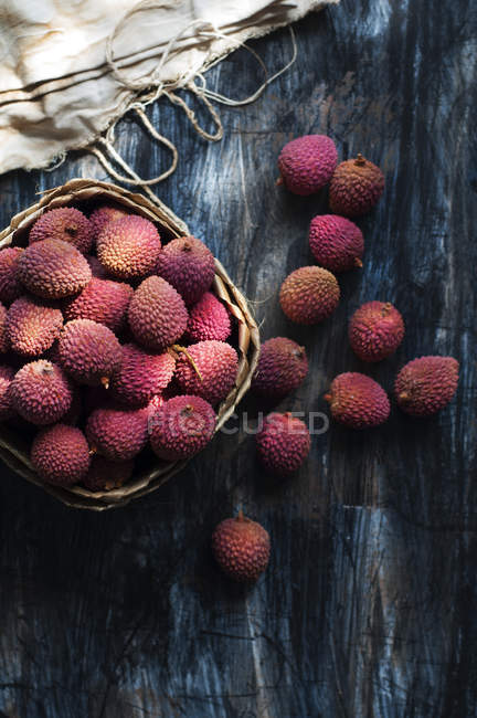 Basket with lychee fruits over wooden table — Stock Photo