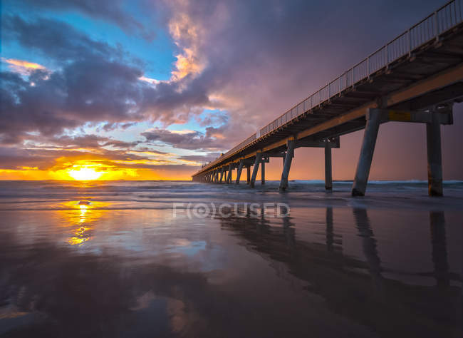 Scenic view of Pier reflection on beach at sunrise, Gold Coast, Queensland, Australia — Stock Photo