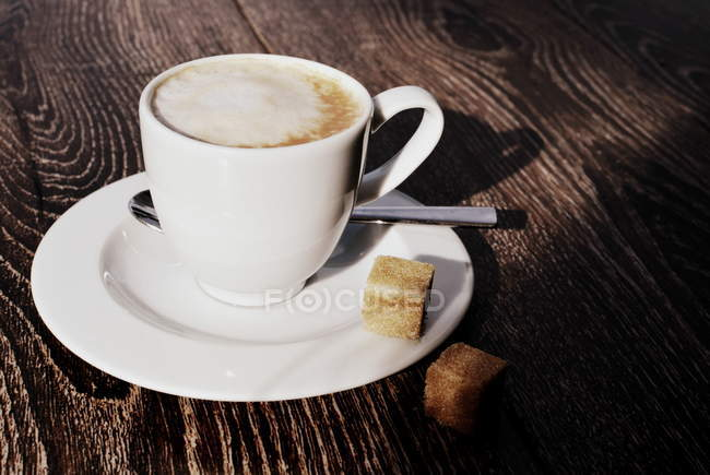 Closeup view of Cappuccino coffee with sugar cubes — Stock Photo