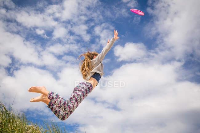 Ragazza che salta per prendere un frisbee — Foto stock