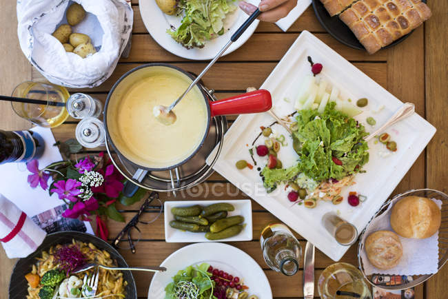 Cheese fondue and vegetables over wooden table — Stock Photo