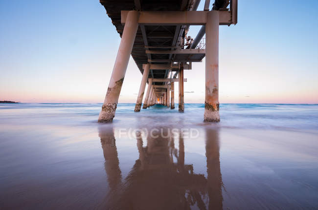 Pier reflection on beach at sunrise, Gold Coast, Queensland, Australia — Stock Photo