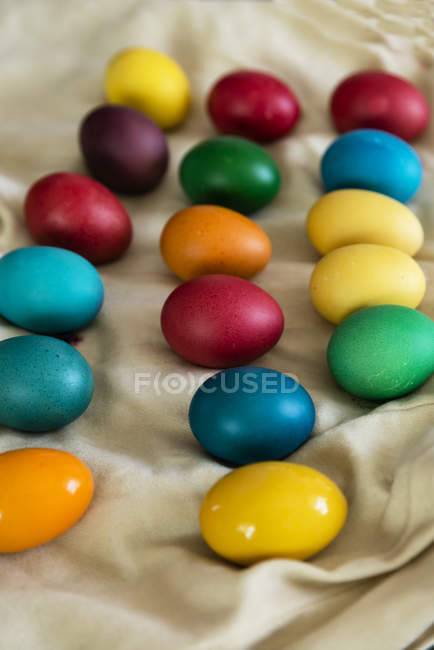 Multi-colored Easter eggs over fabric, closeup — Stock Photo