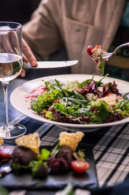 Женщина ест козий сыр и клубничный салат с бокалом белого вина — стоковое фото