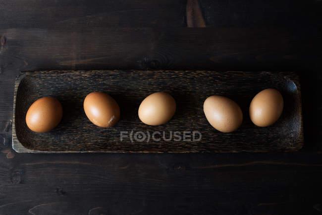 Cinco ovos em um prato de madeira — Fotografia de Stock