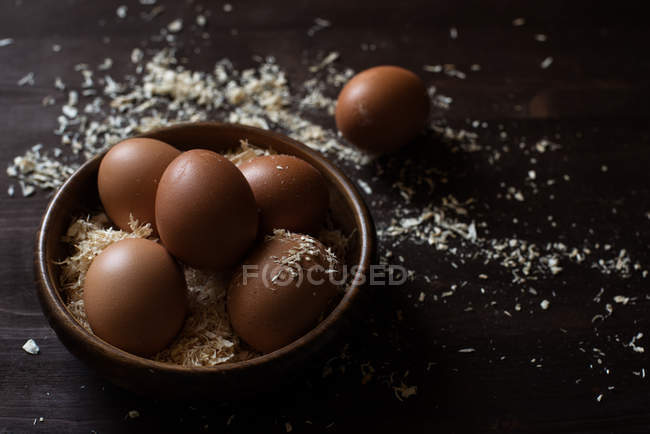 Closeup view of eggs in a wooden bowl with sawdust — Stock Photo