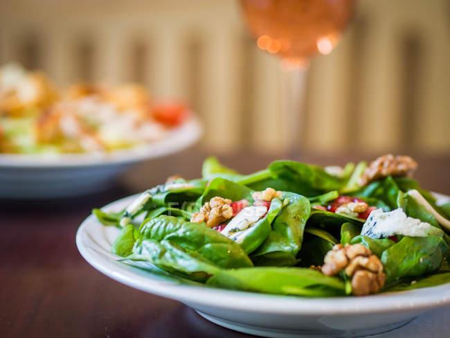 Ensalada de queso azul y espinacas con un vaso de vino de rosas - foto de stock