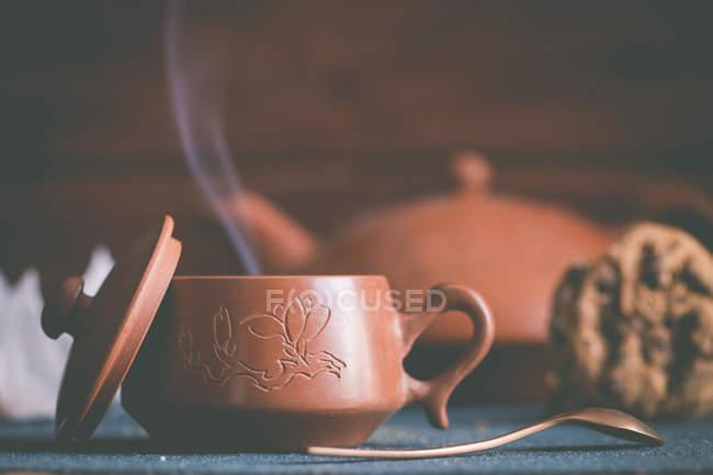 Théière en argile, tasse de thé et un biscuit — Photo de stock