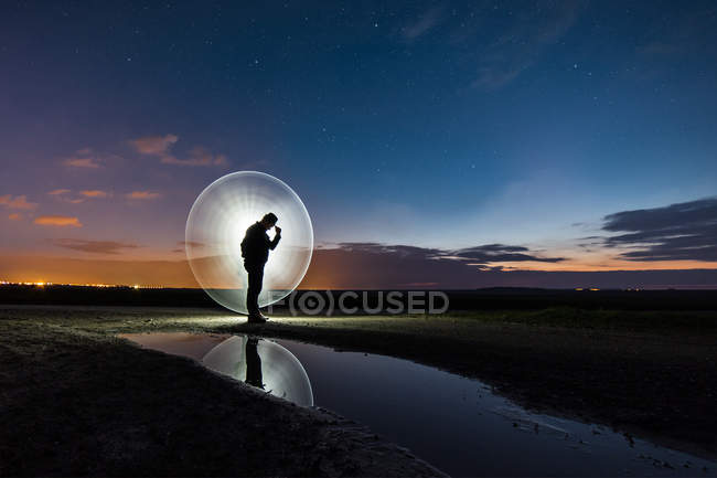 Silhouette of man standing in field surrounded by halo of light — Stock Photo