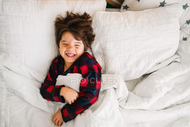 Retrato de un niño acostado en la cama riendo - foto de stock