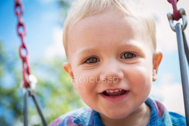 Portrait of a smiling boy on a swing — Stock Photo