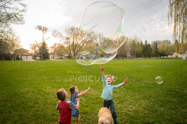 Three children playing with giant soap bubbles — Stock Photo