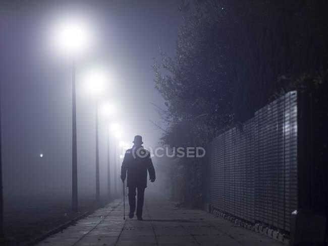 Silhouette of man with a  walking stick walking along foggy street - foto de stock