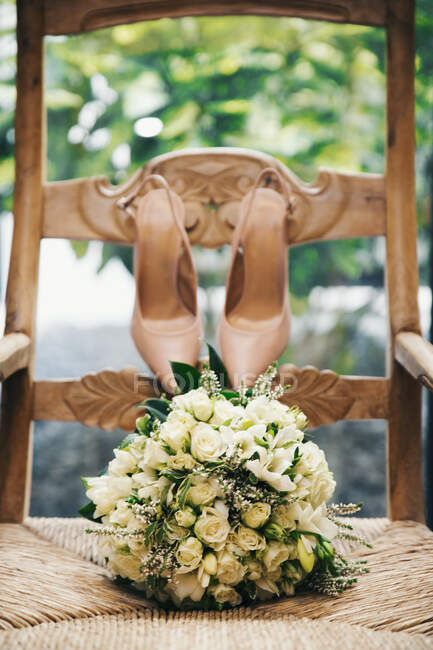 Wedding bouquet and bride's shoes on a chair — Stock Photo