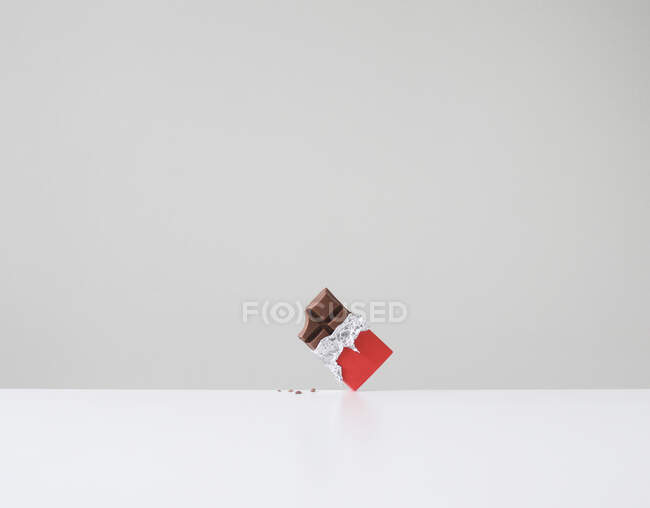Chocolate bar with missing bite and chocolate crumbs on table — Stock Photo