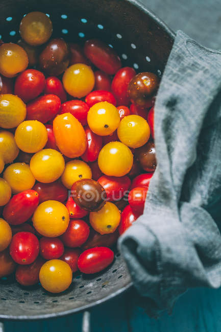 Cherry tomatoes in a colander, closeup view — Stock Photo