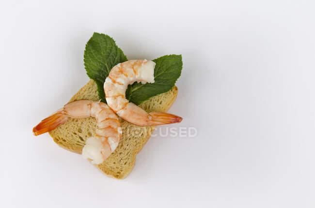 Peeled shrimps on bread toast — Stock Photo