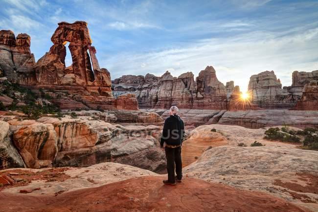 Homem olhando para Arch Druid no pôr do sol, Parque Nacional Canyonlands, Utah, América, Estados Unidos da América — Fotografia de Stock