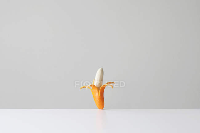 Conceptual banana in an orange skin — Stock Photo