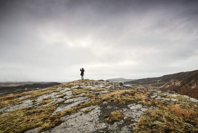 Vista trasera de la mujer de pie en la colina tomando una foto, Islandia - foto de stock
