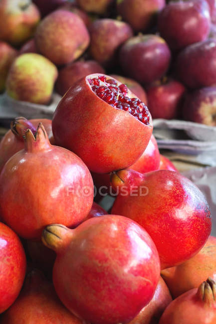 Closeup of pomegranates and apples at a food market — Stock Photo