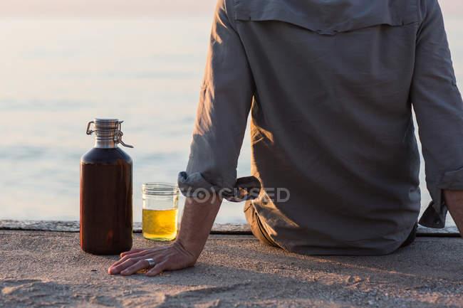Uomo seduto sul molo vicino alla spiaggia con una birra — Foto stock