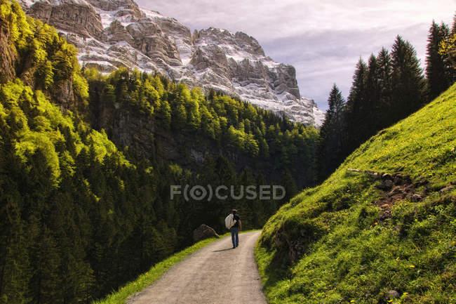 Man walking along mountain road, Seealpsee, Appenzell Innerrhoden, Switzerland — Stock Photo