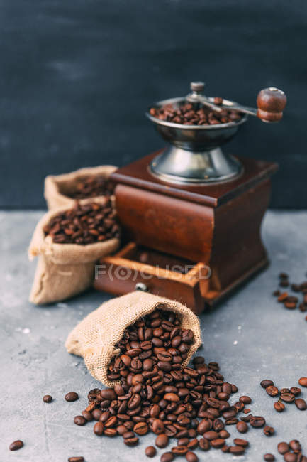 Coffee grinder with sacks of coffee beans — Stock Photo
